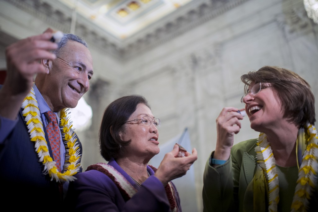 From left, Sen. Chuck Schumer (D-NY) Sen. Mazie Hirono (D-HI) and Sen. Amy Klobuchar (D-MN) taste the spam musubi during the Taste of Hawaii event. (Photo By Bill Clark/CQ Roll Call)