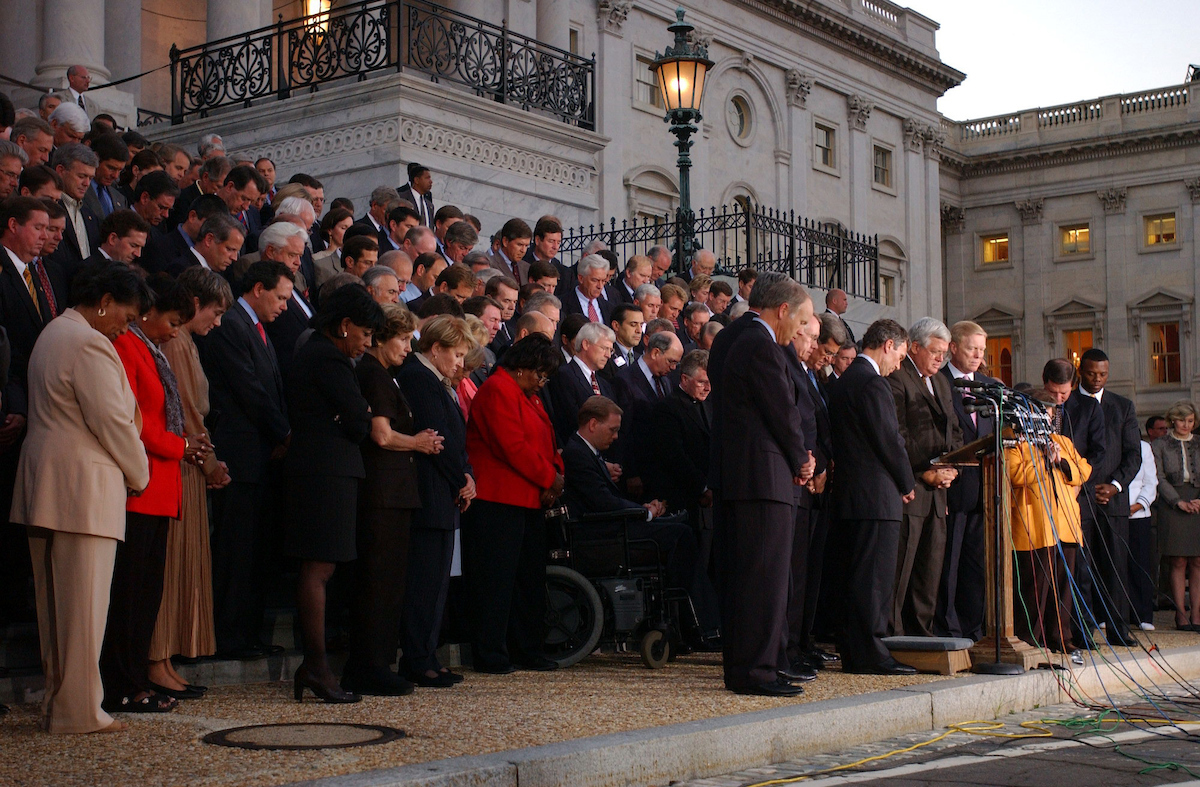 House Speaker J. Dennis Hastert is joined by congressional leadership and members of Congress in prayer on the steps of the Capitol the evening of Sept. 11, 2001. The lawmakers denounced the terrorist attacks and resolved to keep the government open. (CQ Roll Call archive photo)