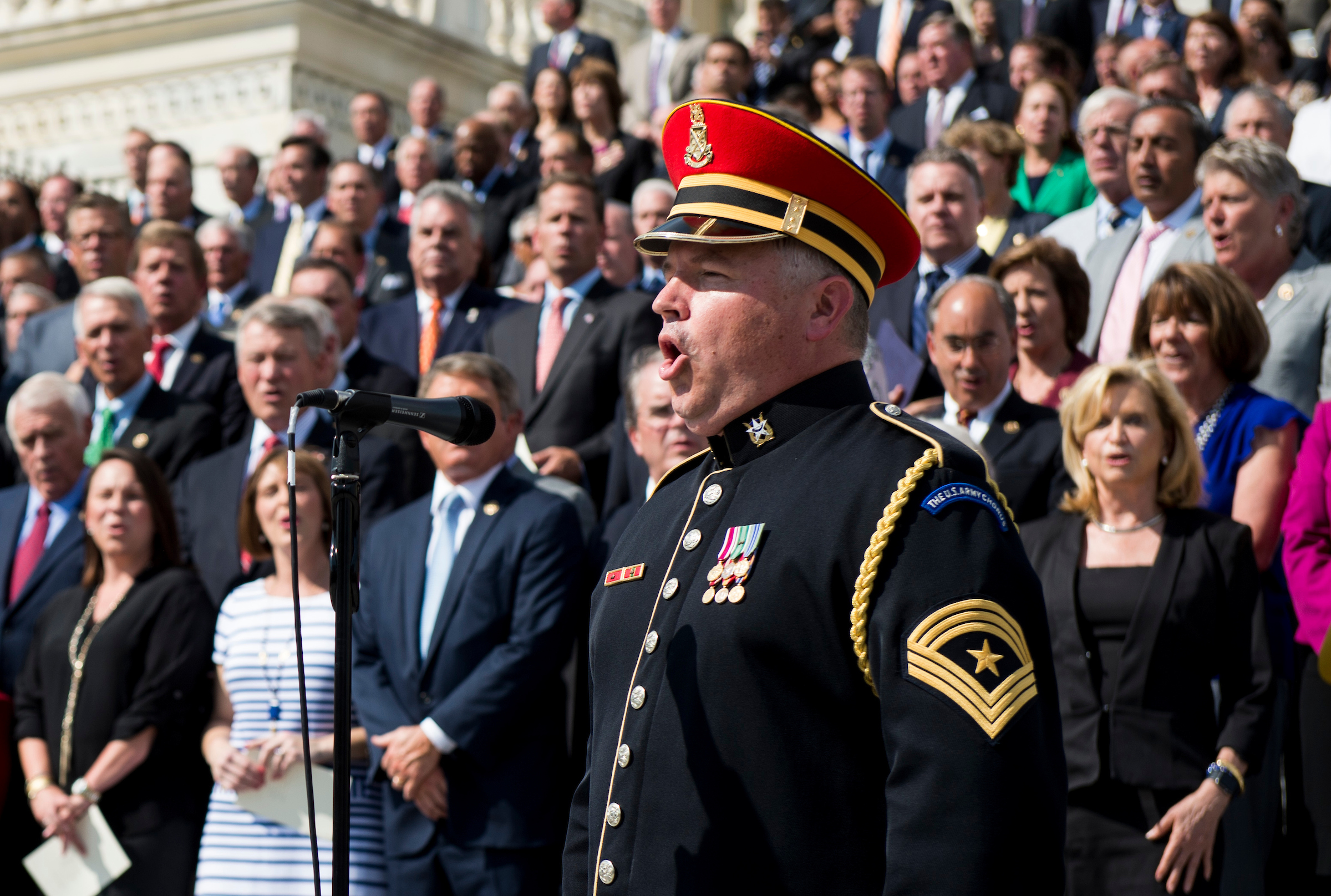 A member of the U.S. Army Chorus leads members of Congress in the singing of God Bless America at the conclusion of the ceremony on the House steps to mark the 15th anniversary of 9/11on Friday, Sept. 9, 2016. (Bill Clark/CQ Roll Call)
