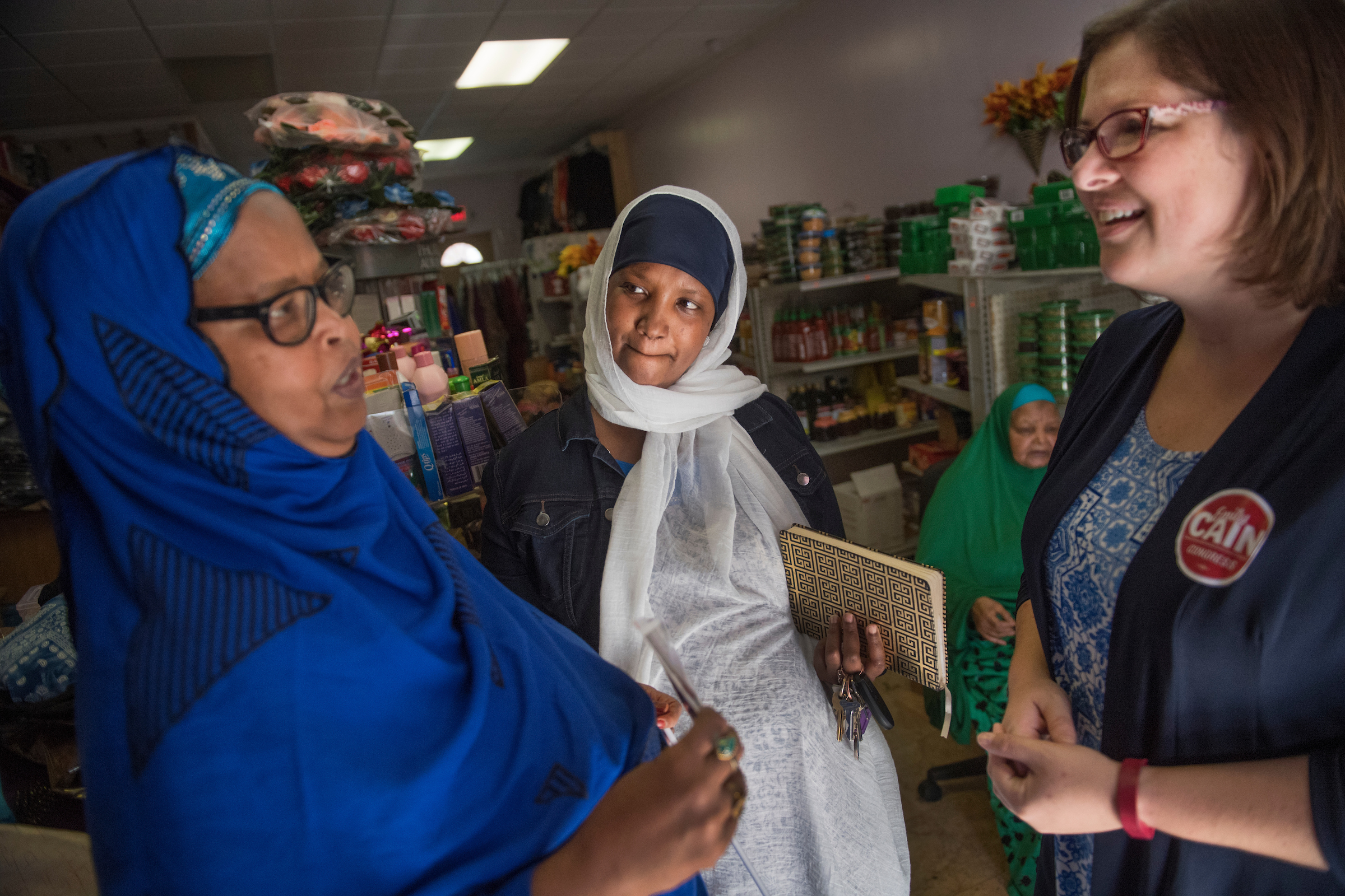 Cain talks with Ansia Dol, right, and Fatuma Hussein, center, both from Somali, at the Al Madina Variety & Halal Store in Lewiston, Maine, last week. (Tom Williams/CQ Roll Call)