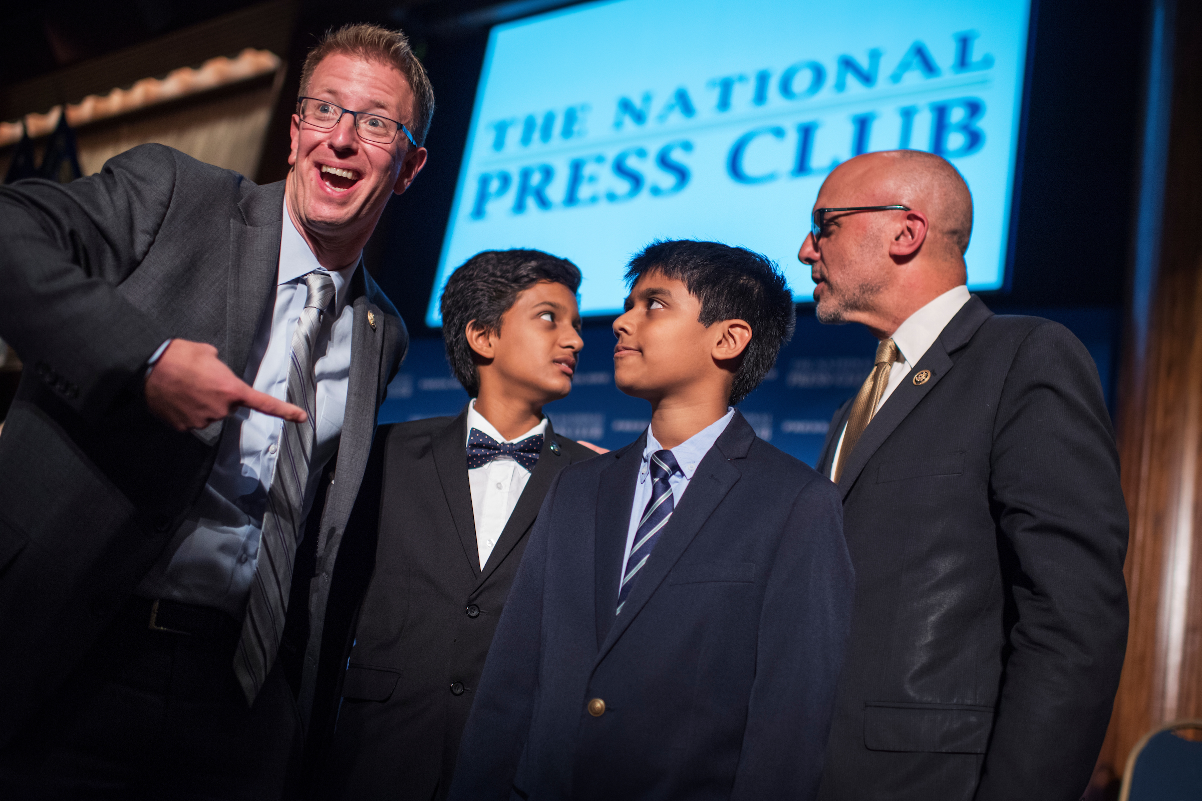 Reps. Derek Kilmer of Washington, far left, and Ted Deutch, far right, of Florida, talk with co-champions of the 2016 Scripps National Spelling Bee Jairam Hathwar, 13, left, and Nihar Janga, 11, before the Politicians vs. Press Spelling Bee at the National Press Club on Wednesday, Sept. 21. (Tom Williams/CQ Roll Call)