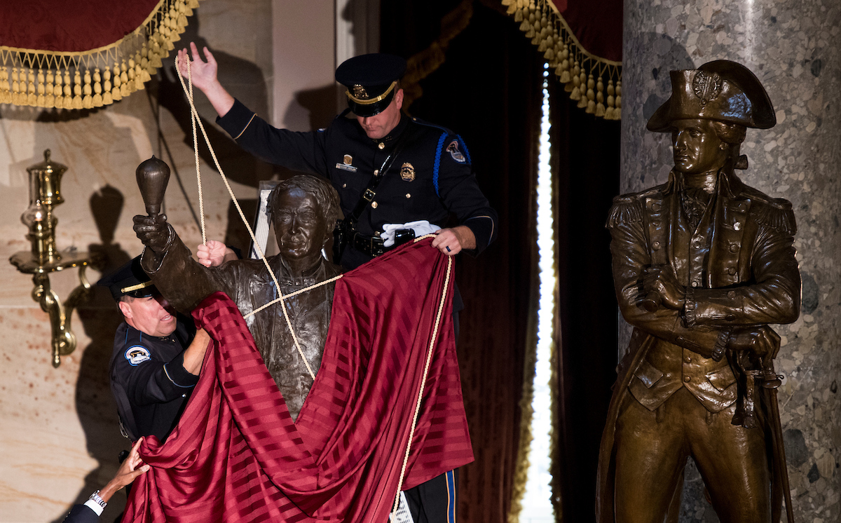 After fabric covering the Thomas Edison statue prematurely dropped, members of the U.S. Capitol Police Honor Guard help refit the sheet before the start of the unveiling ceremony for the statue in Statuary Hall in the Capitol on Wednesday, Sept. 21. (Bill Clark/CQ Roll Call)