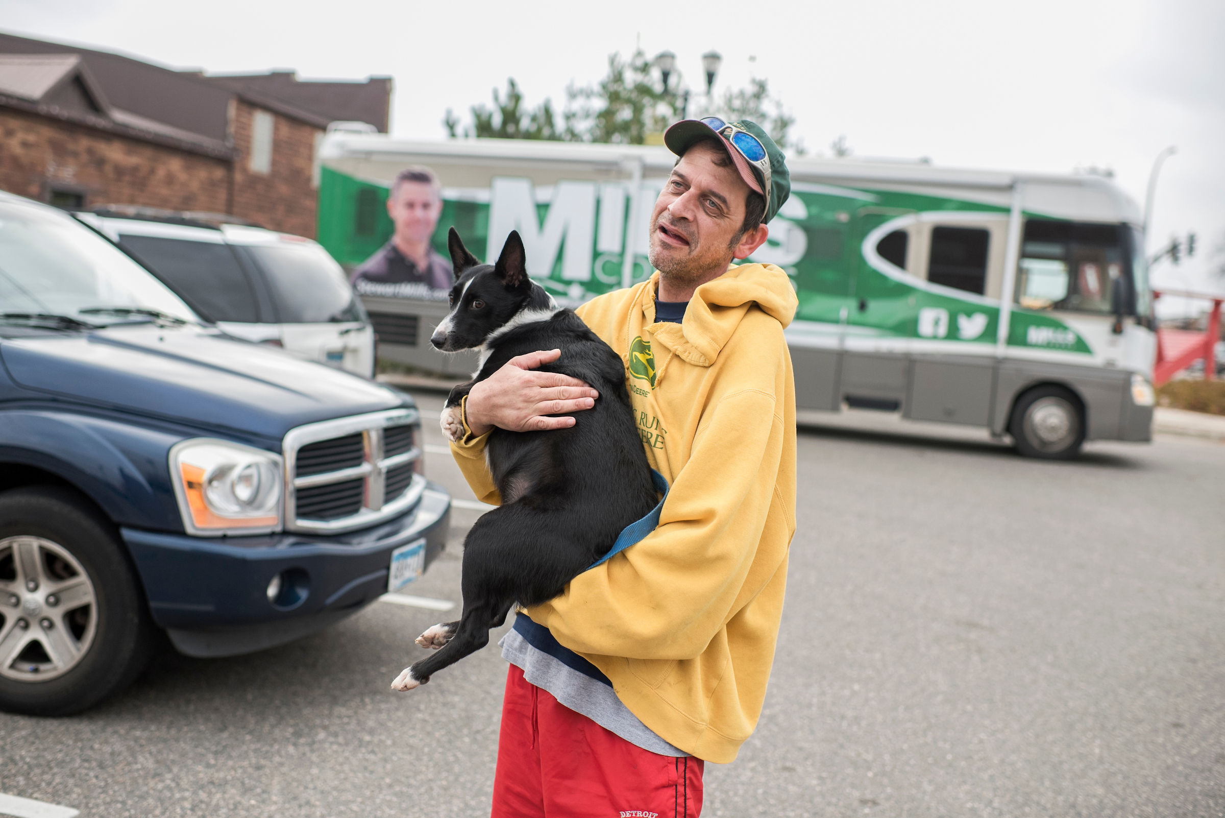 Tom Kearney, a Mills supporter, prepares for a photo with his dog Jazzmyne, in front of Mills' bus in Grand Rapids, Minn. (Tom Williams/CQ Roll Call)
