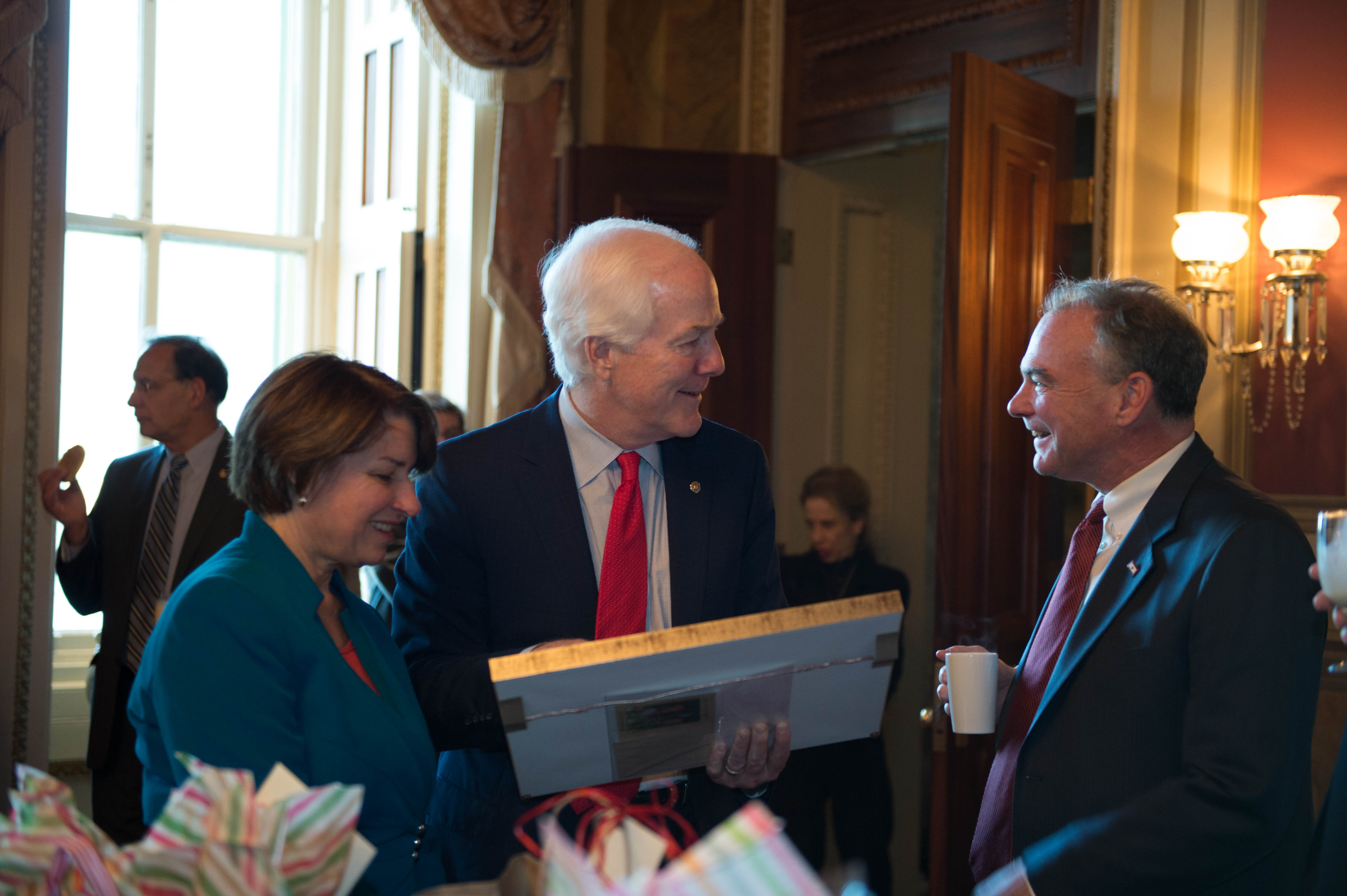 From left to right: Sen. Amy Klobuchar, D-Minn., Sen. John Cornyn, R-Texas, Sen. Tim Kaine, D-Va., at the holiday gift exchange. (Photo courtesy of Senate Democrats)