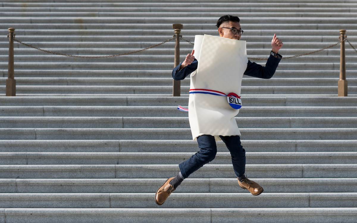 "26. Oct. 31: Rene T, who declined to provide his full last name, wears a ""Bill on Capitol Hill"" costume as he jumps in the air while a friend takes photos on the U.S. Senate steps at the U.S. Capitol on Halloween. (Bill Clark/CQ Roll Call file photo)"