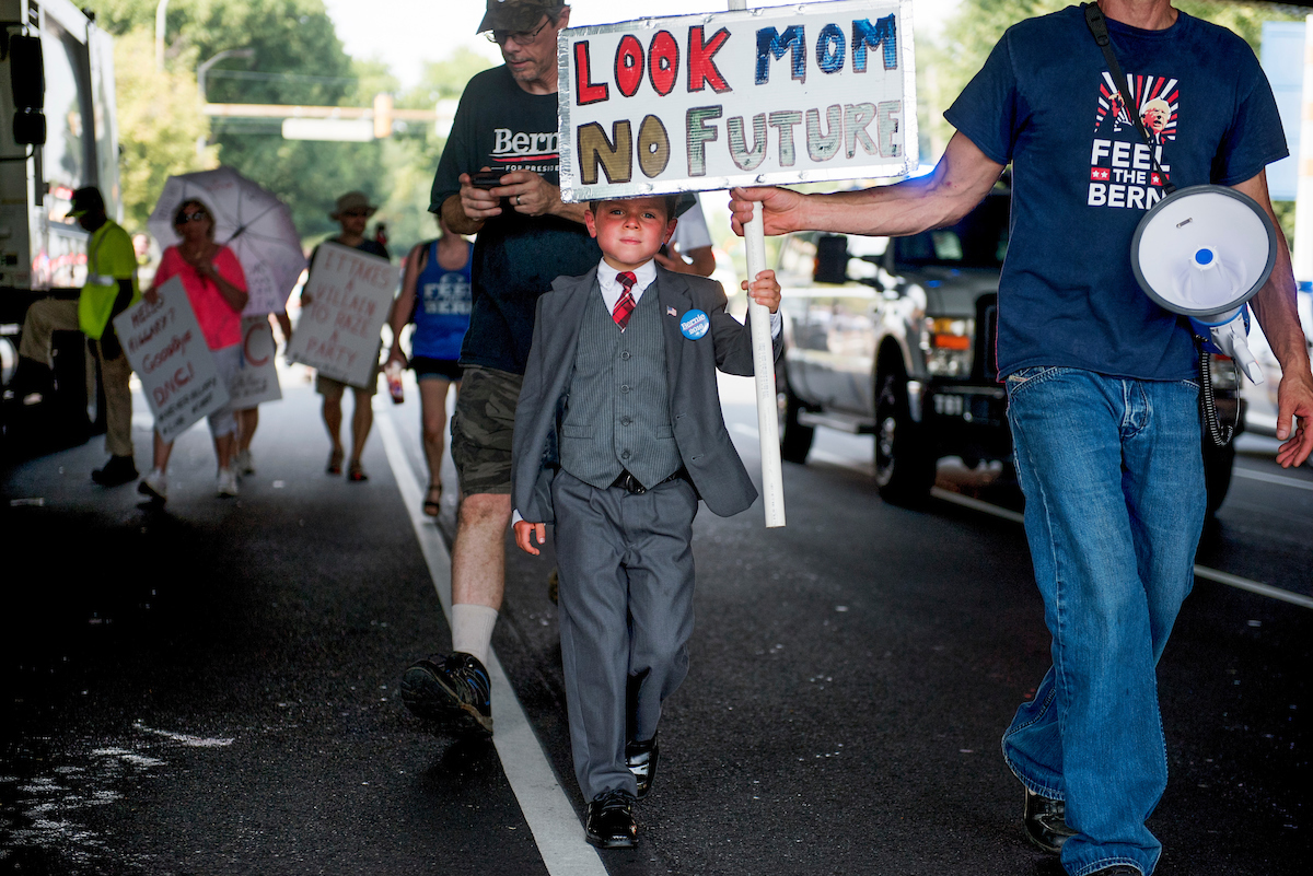 "16. July 25: Connor Garrett, 9, of Connecticut, and his father, Dan, walk down Broad Street during a march by supporters of Vermont Sen. <a class=""memberLink"" title=""Click to view member info in a new window"" href=""http://data.rollcall.com/members/509?rel=memberLink"" target=""_blank"">Bernie Sanders</a> on the first day of the Democratic National Convention in Philadelphia. (Tom Williams/CQ Roll Call file photo)"