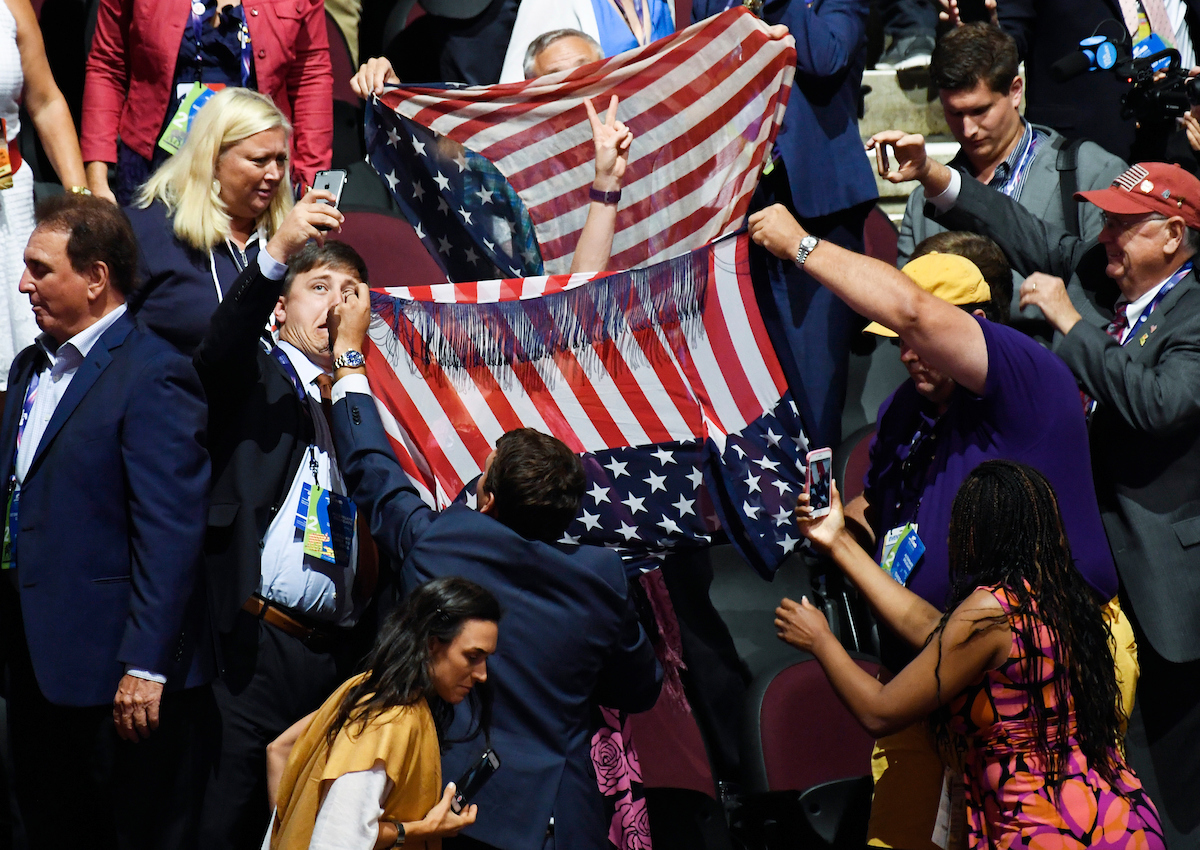 12. July 19: A man attempts to take a selfie as GOP convention attendees try to cover an anti-Trump protester with American flags inside the Quicken Loans Arena in Cleveland at the 2016 Republican National Convention. (Bill Clark/CQ Roll Call file photo)