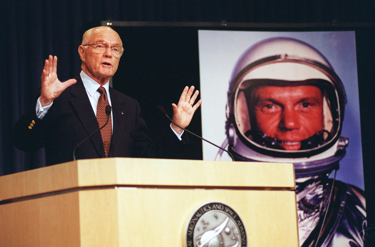 Jan. 16, 1998: Sen. John Glenn, D-Ohio, during a press conference at NASA headquarters in Washington, D.C., announces his return to the space program. In the background is a 1962 photo of Glenn in his space-flight suit. He is slated to fly aboard the space shuttle in October. (Photo by Douglas Graham/CQ Roll Call File Photo)