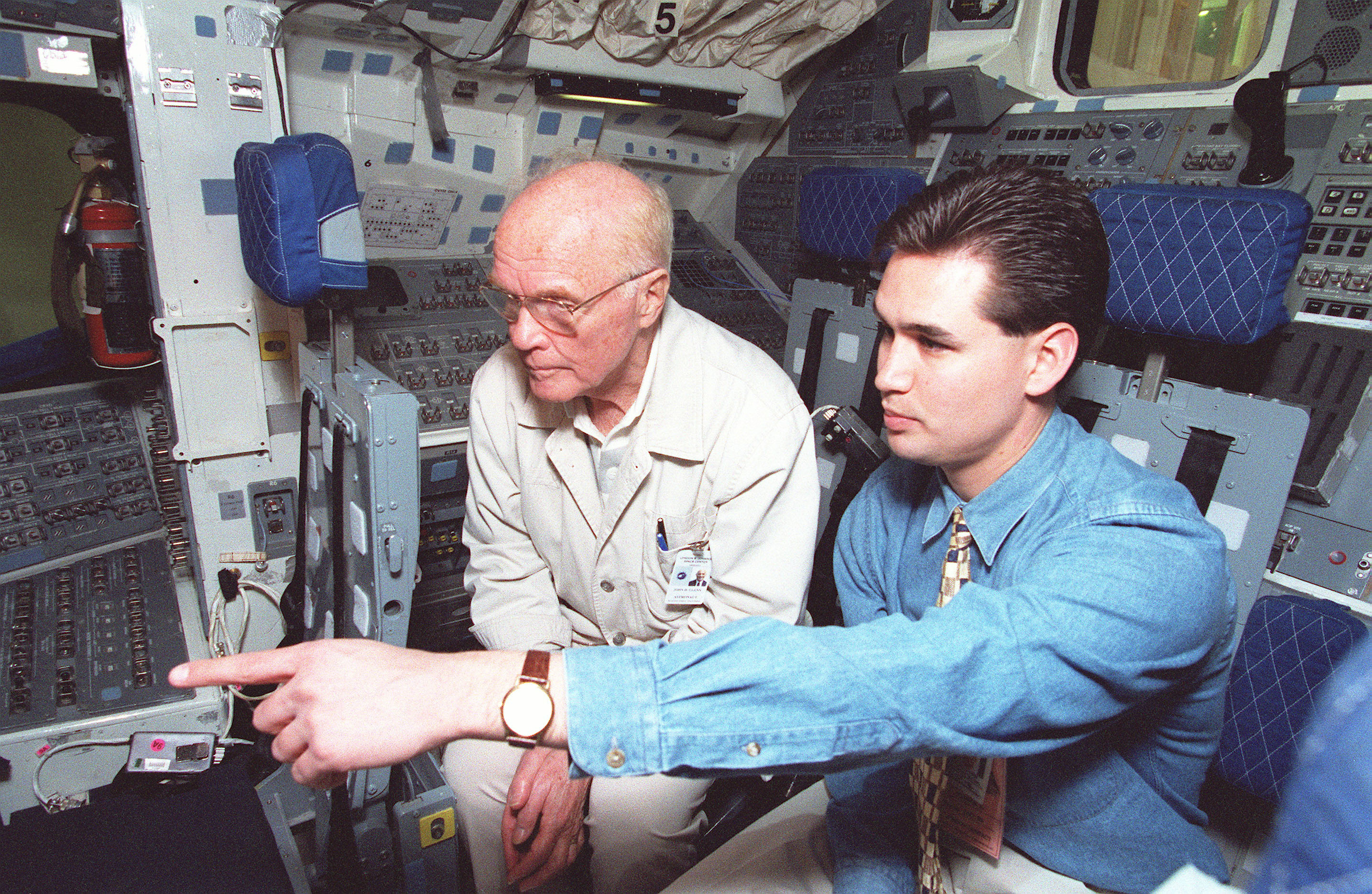 April 1998: Sen. John Glenn, D.-Ohio, is seated on the flight deck of the crew compartment trainer while being briefed by crew trainer Adam Flagler. Flagler is pointing toward the displays and controls at the commander's station, forward cabin. Glenn has begun training at the Johnson Space Center for the STS-95 space flight, scheduled for launch later in the year. (Photo courtesy of NASA)