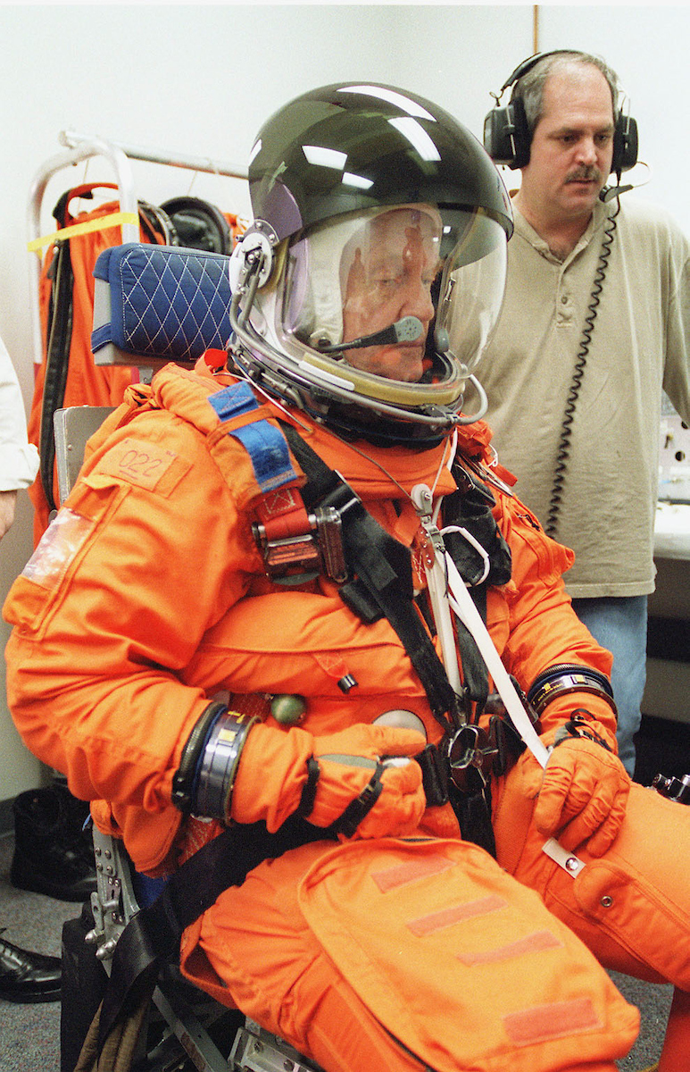 April 1998: Sen. John Glenn, D-Ohio, with assistance from Boeing suit technician Lloyd Armintor, applies final touches during suit donning at the flight equipment processing lab for the Johnson Space Center. This was Glenn's first interface with the partial pressure launch and entry suit since being named to fly aboard the Space Shuttle Discovery on the STS-95 mission. (Photo Courtesy of NASA)