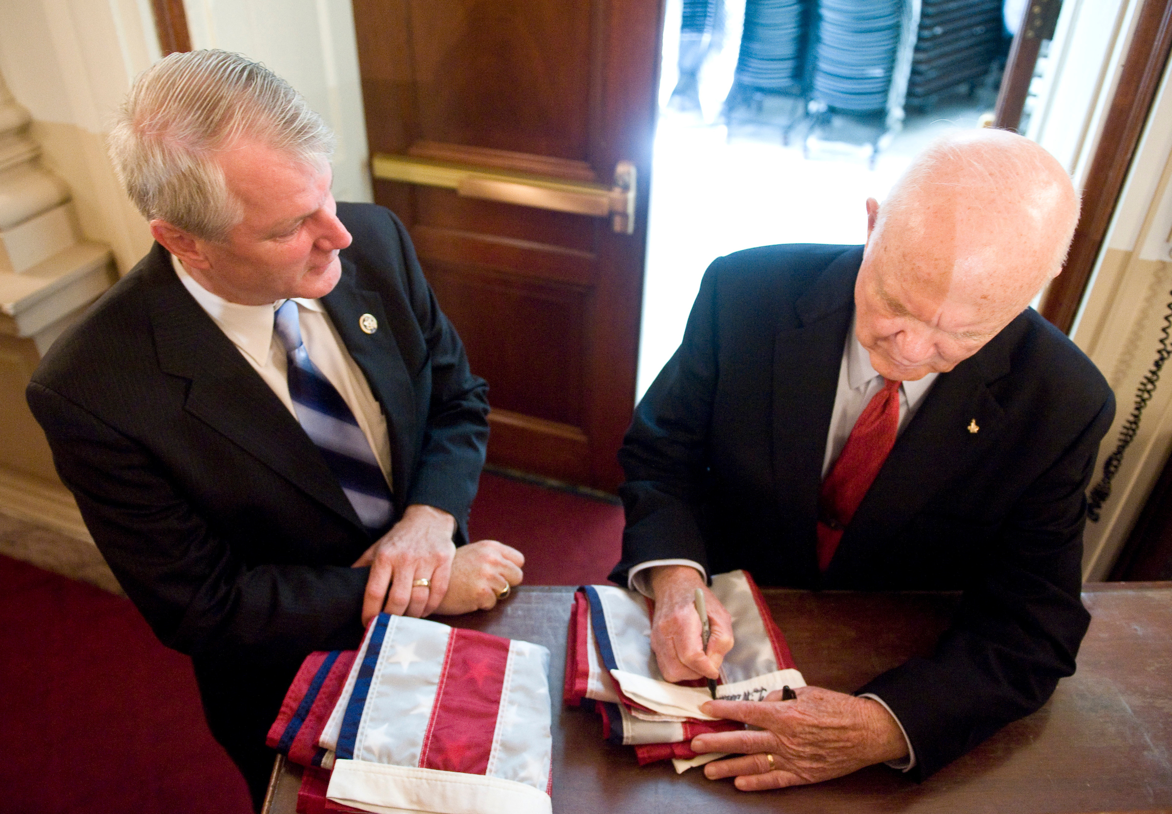 July 21, 2009: Rep. Brian Baird, D-Wash., left, watches as astronaut and former Sen. John Glenn, D-Ohio, signs two flags for Baird's twin sons during the tribute event to the Apollo 11 astronauts celebrating the 40th anniversary of the first moon landing on. (CQ Roll Call File Photo)
