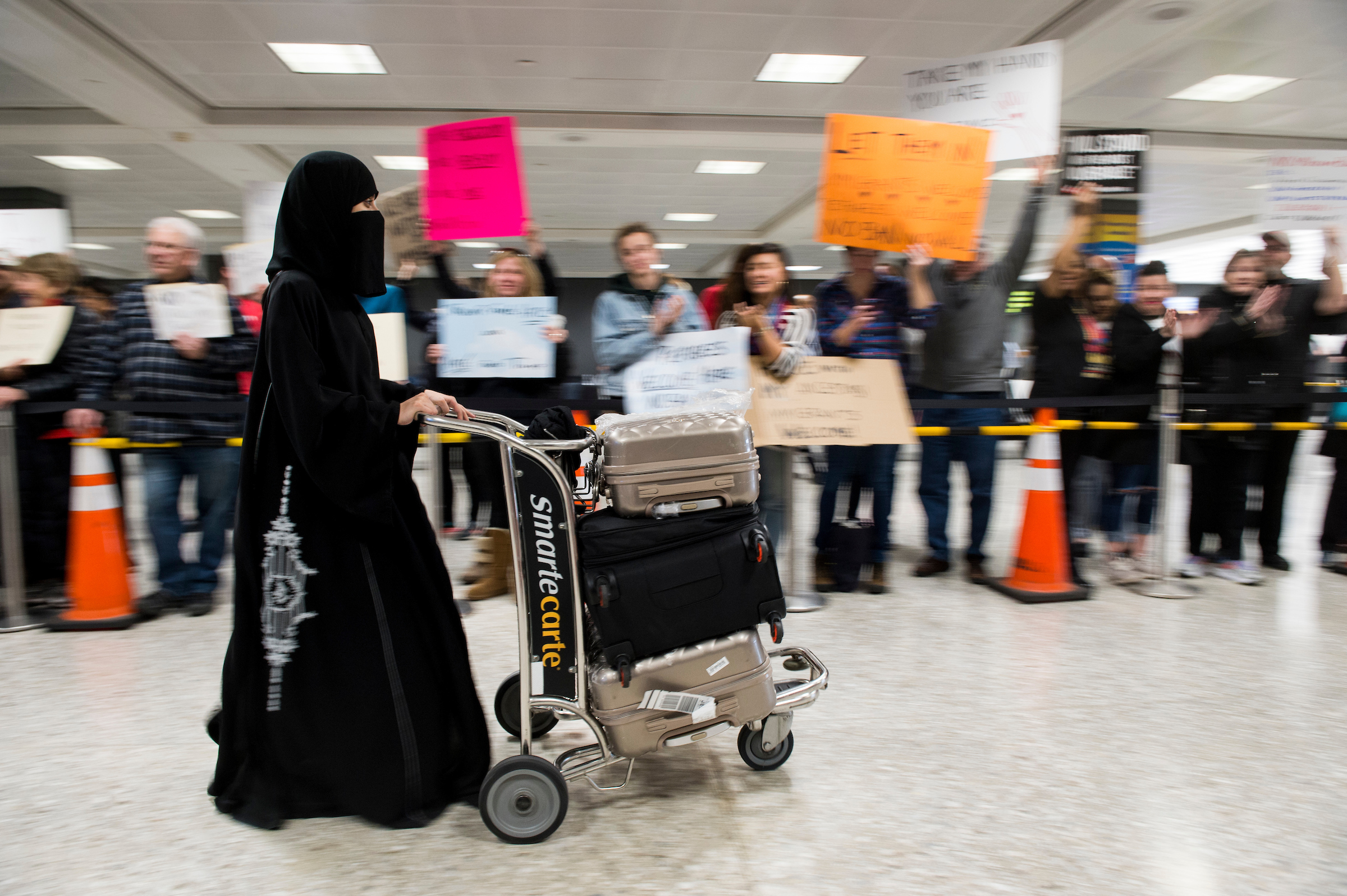 UNITED STATES - JANUARY 29: Passengers from a Saudi Arabian Airlines flight from Jeddah are greeted by protesters as they arrive at Dulles International Airport in Virginia on Sunday, Jan. 29, 2017. Protests erupted at airports around the country following President Trump's executive order restricting travel from several Islamic countries. (Photo By Bill Clark/CQ Roll Call/Pool)