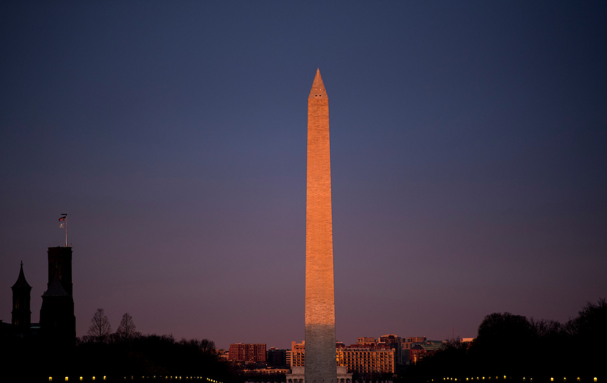 A brief burst of sunlight hits the Washington Monument at sunrise on Thursday. (Bill Clark/CQ Roll Call)