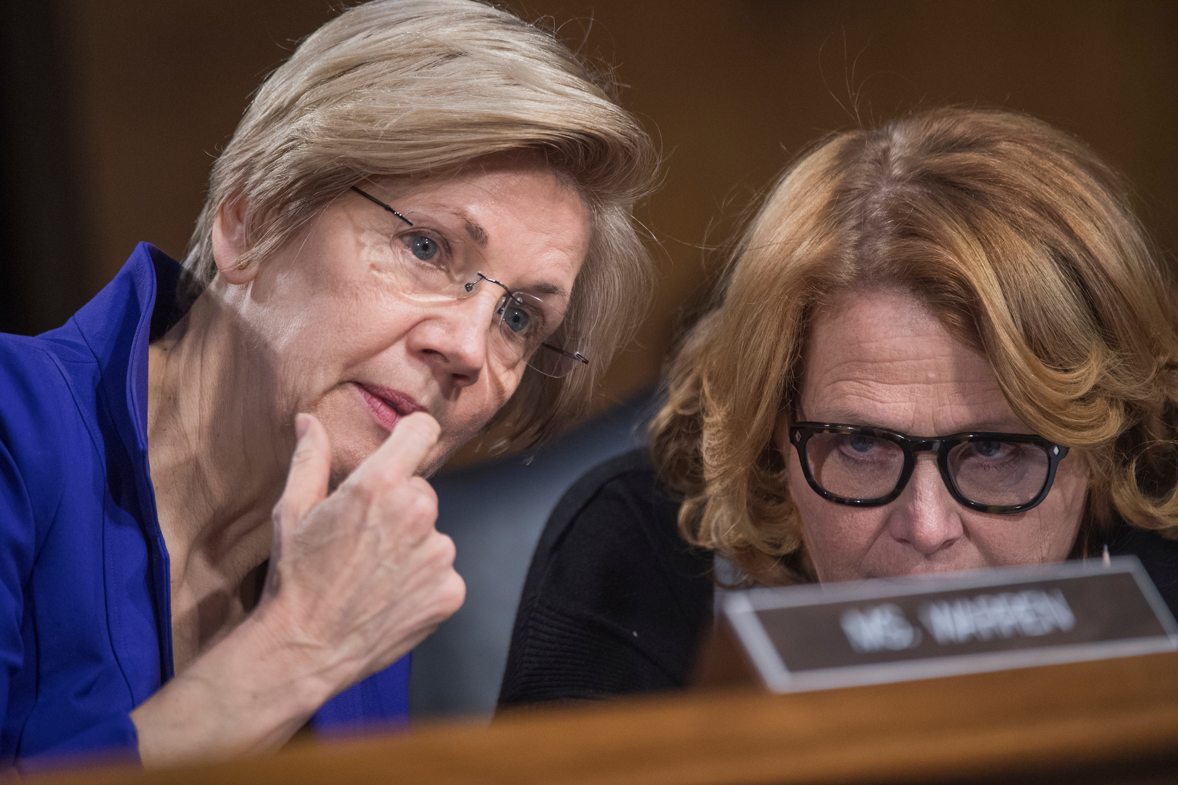 """UNITED STATES - FEBRUARY 14: Sens. Elizabeth Warren, D-Mass., left, and Heidi Heitkamp, D-N.D., talk during a Senate Banking, Housing, and Urban Affairs Committee hearing in Dirksen Building titled """"The Semiannual Monetary Policy Report to the Congress,"""" featuring testimony by Fed Chairwoman Janet Yellen, February 14, 2017. (Photo By Tom Williams/CQ Roll Call)"""