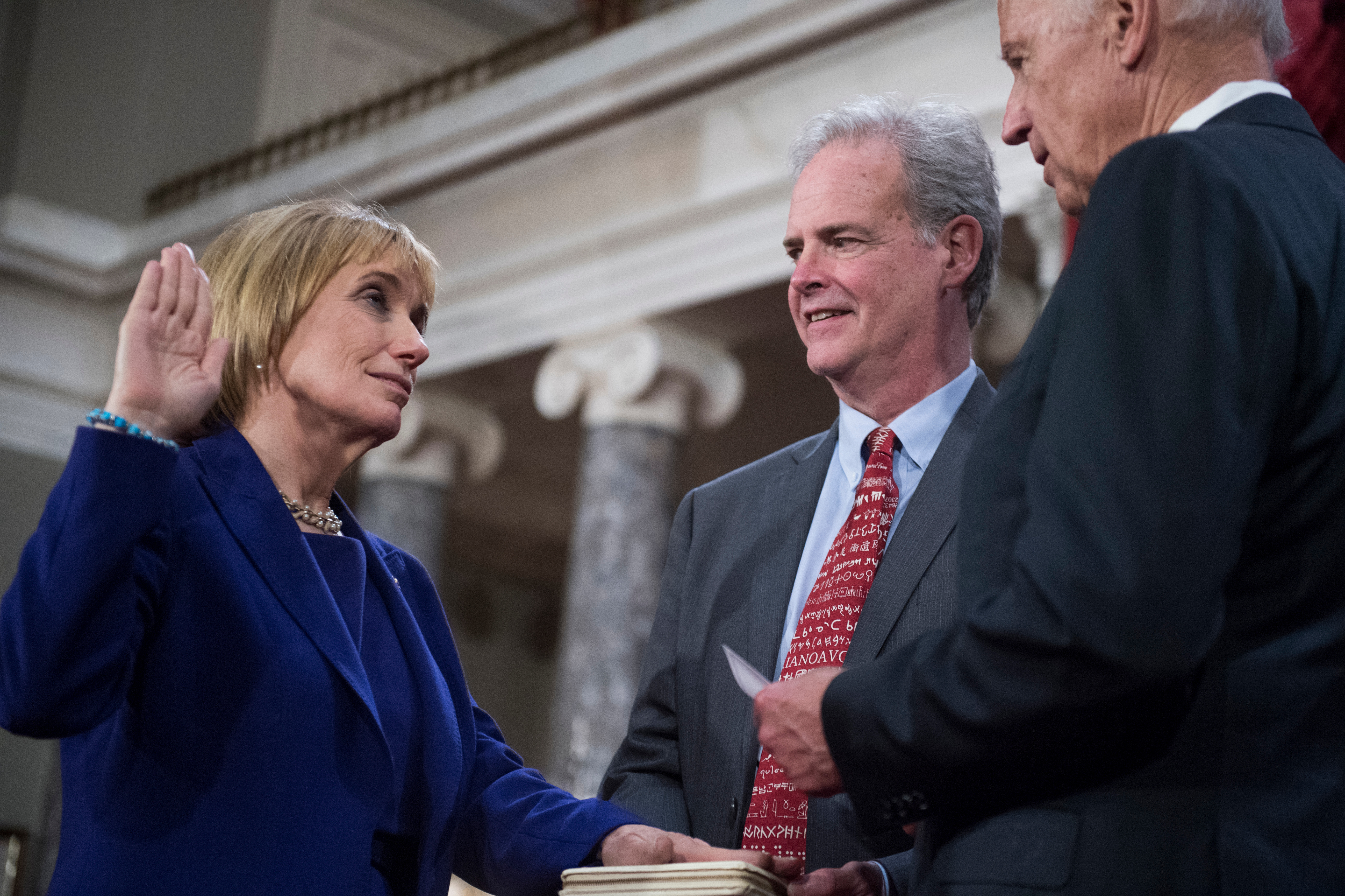 Hassan is sworn in on Jan. 3 by Vice President Joseph R. Biden Jr. as her husband Tom looks on. (Tom Williams/CQ Roll Call file photo)