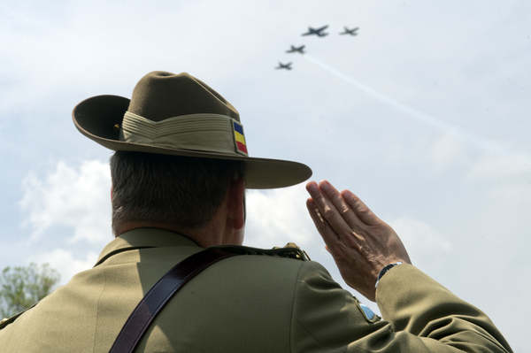 Brigadier Gen. David Creagh of Australia, watches World War II era aircraft as they fly over the World War II Memorial. (Tom Williams/CQ Roll Call)