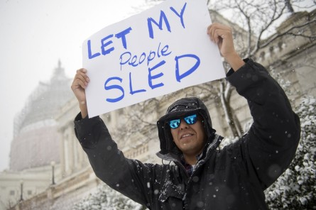UNITED STATES - MARCH 05: Hill staffer Brandon Ashley holds a sign of protest on the west front lawn of the Capitol during a snow storm, March 5, 2015. The Capitol Police informed people gathering of the ban on sledding in the area but most choose to ignore the warning. (Photo By Tom Williams/CQ Roll Call)