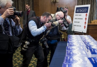 News photographers take photos of the budget documents. (Bill Clark/CQ Roll Call)