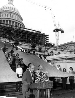 """DRAPED IN DENIM, 50 employees of the Blue Bell plant hold world's largest jeans (big enough to accommodate zipper above) at the Capitol. Rep. Howard Coble (NC) and Blue Bell president Ed Bauman are at the mikes, explaining pants, 54 feet long, 35 feet wide, with 400 inch waist and weighing 200 pounds , contain 16,000 signatures supporting textile and apparel limitations."""