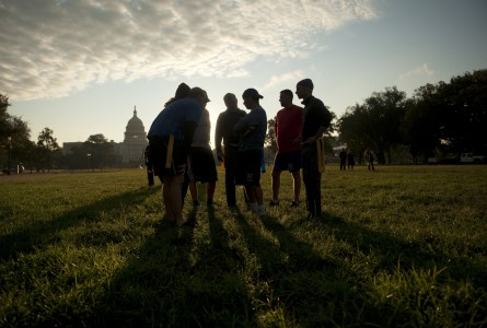 Members of Congress and staffers huddle during a congressional football practice on the Mall in preparation for the upcoming game between members of Congress and the Capitol Police. (Tom Williams/CQ Roll Call File Photo)