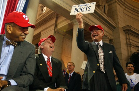 The late Charlie Brotman, former announcer for the Washington Senators, holds up a license plate celebrating the move of the Montreal Expos to Washington at a November 2004 event announcing the team's renaming to Nationals. (CQ Roll Call file photo.)