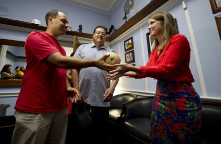 Giev Kashkooli vice president and Ramon Ramirez president of the Farmer Workers United in August 2013 talk with and deliver a cantaloupe picked by migrant workers to Sarah Wells of Rep. Steve King's office in response to his disrespectful comments about immigrants. (Douglas Graham/CQ Roll Call File Photo)