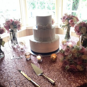 "The wedding cake had a ""Kate Spade inspired look,"" and sat atop rose-gold sparkly table linens to match the bride's rose-gold Kate Spade pumps. (photo courtesy Tiffany McGuffee)"